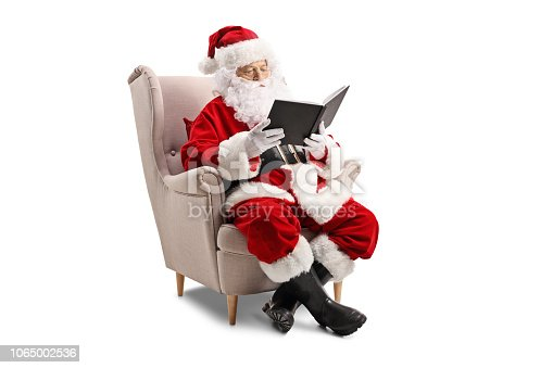 istock Santa Claus sitting in an armchair and reading a book 1065002536