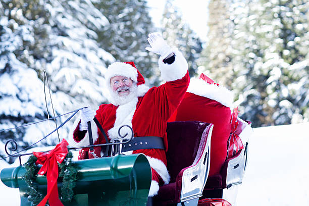 Santa Claus Sitting in His Sleigh Waving Santa Claus at the North Pole sitting in his sleigh waving to the camera. Copy space. sled stock pictures, royalty-free photos & images
