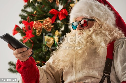 istock Santa Claus sitting in rocking chair near Christmas Tree 491381108