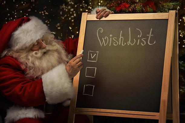 weihnachtsmann sitzend in der nähe von tafel mit wunschliste - weihnachts wunschliste stock-fotos und bilder
