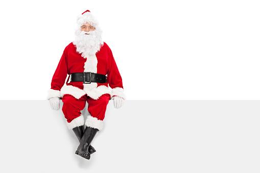istock Santa Claus sitting on a blank billboard 519867679