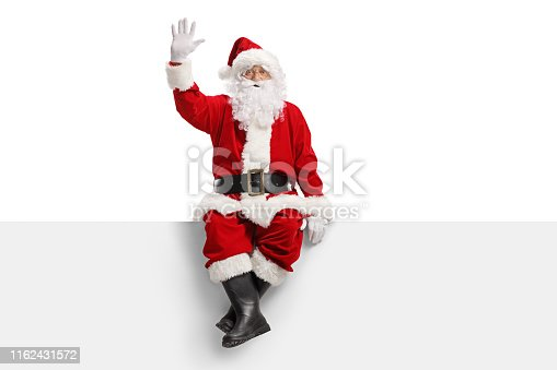 Full length portrait of santa claus sitting on a panel and waving isolated on white background