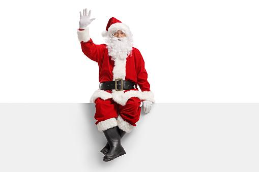 Weihnachtsmann Sitzt Auf Einer Tafel Und Winkt Stockfoto und mehr Bilder von Alter Erwachsener
