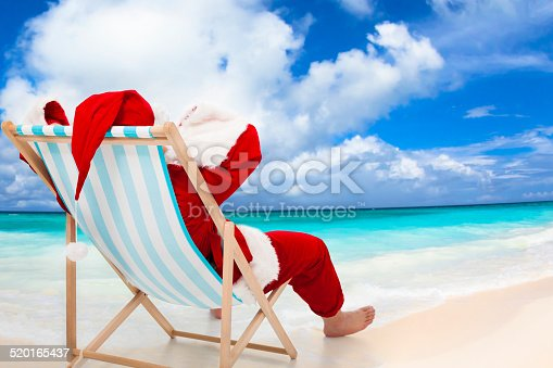 istock Santa Claus sitting on beach chairs. Christmas holiday concept. 520165437