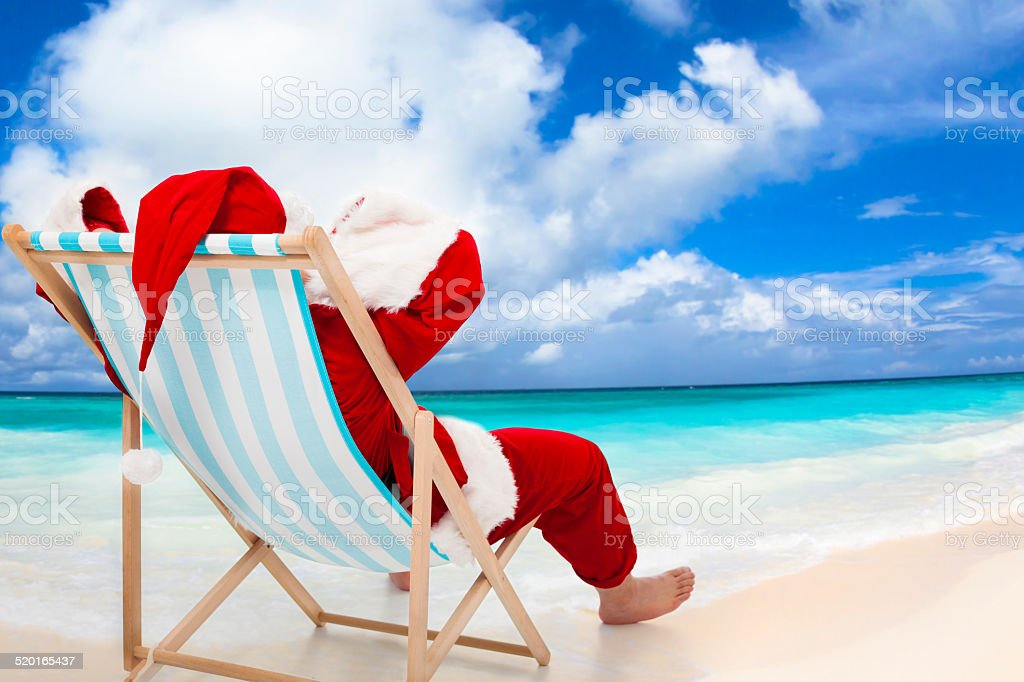 Santa Claus sitting on beach chairs. Christmas holiday concept. stock photo