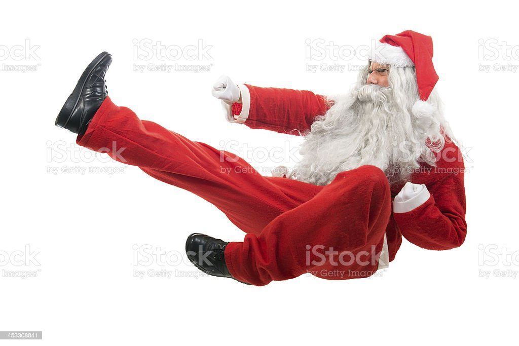 Santa Claus sitting on floor, mimicking karate moves stock photo