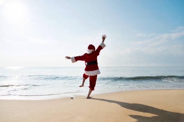 Santa Claus standing on sea beach with arms raised stock photo