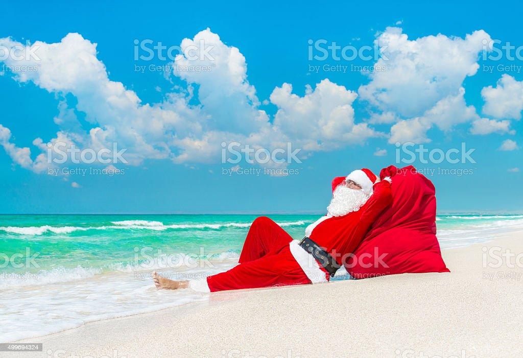 Santa Claus sunbathing at sack full of gifts at beach stock photo