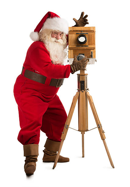 Santa Claus taking picture with old wooden camera stock photo