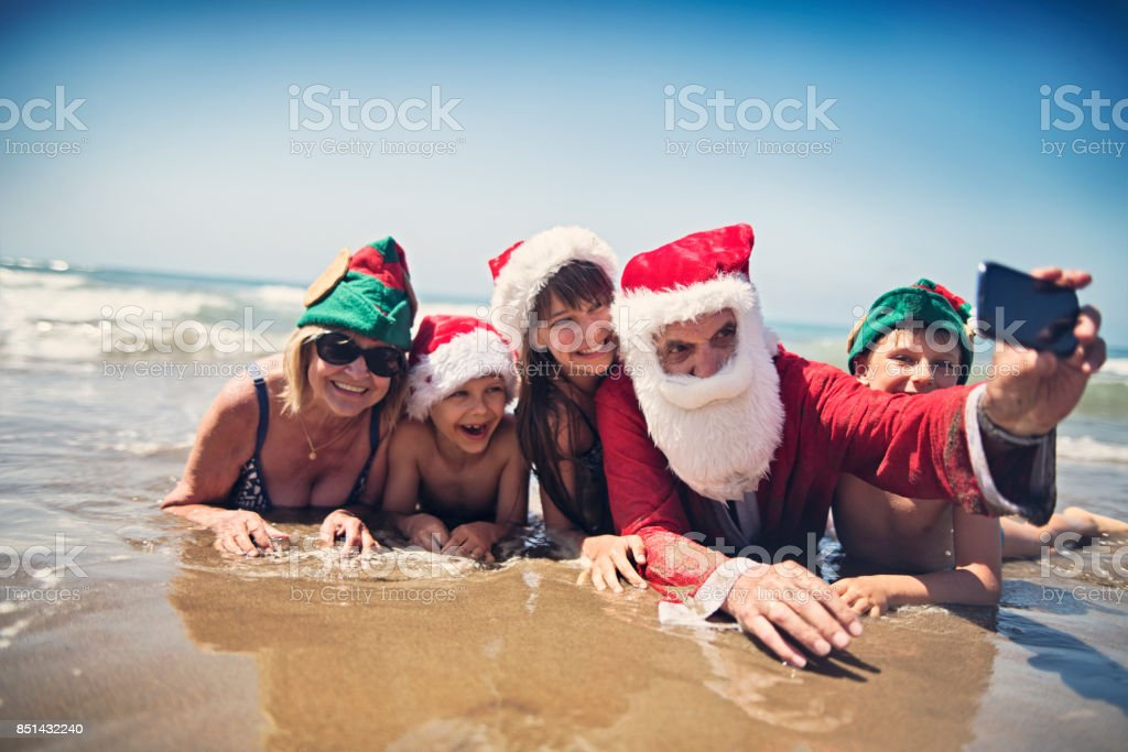 Santa claus taking selfie with family on beach stock photo