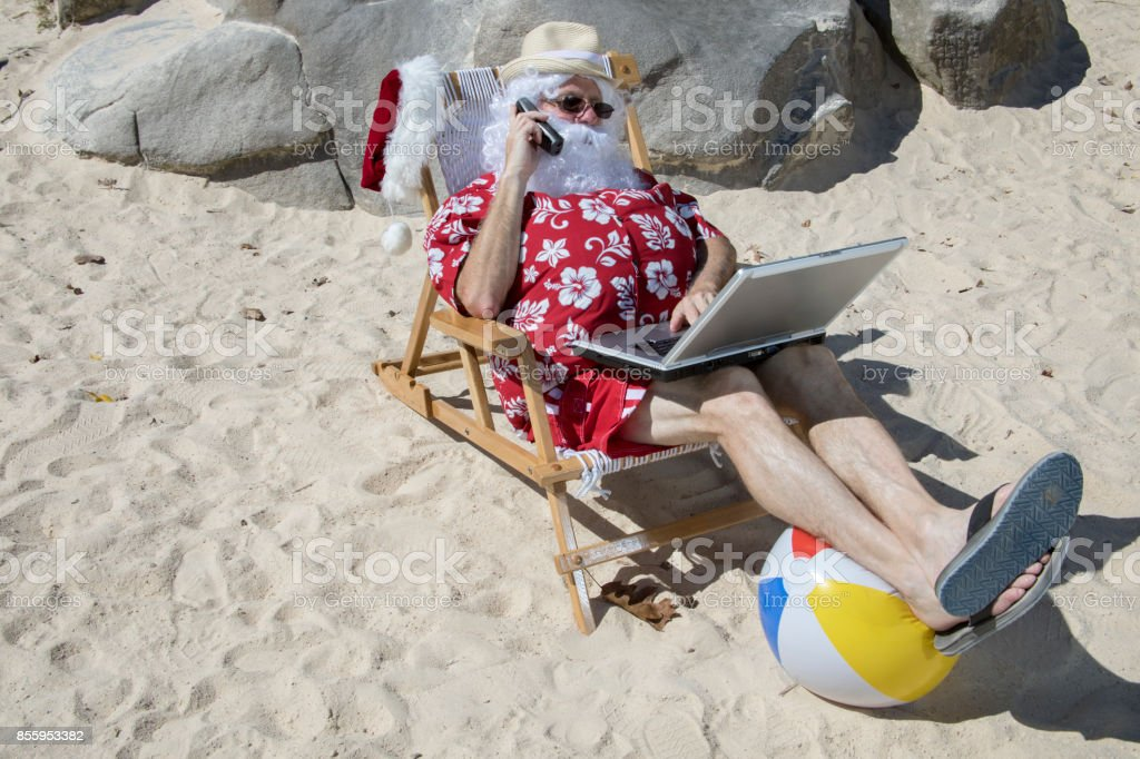 Santa Claus talking on the phone on beach with laptop stock photo