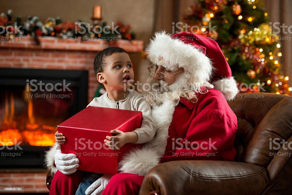 Santa Claus talking to African American little boy at home. stock photo