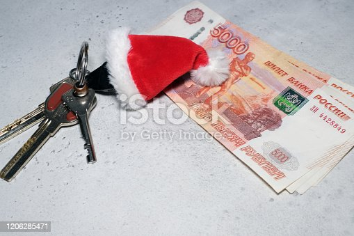istock Santa Claus theme: Santa's hand holding the keys to a new appartament 1206285471