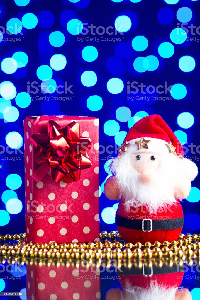Santa Claus toy, gift in package and golden beads on a glass table with a beautiful blue bokeh stock photo