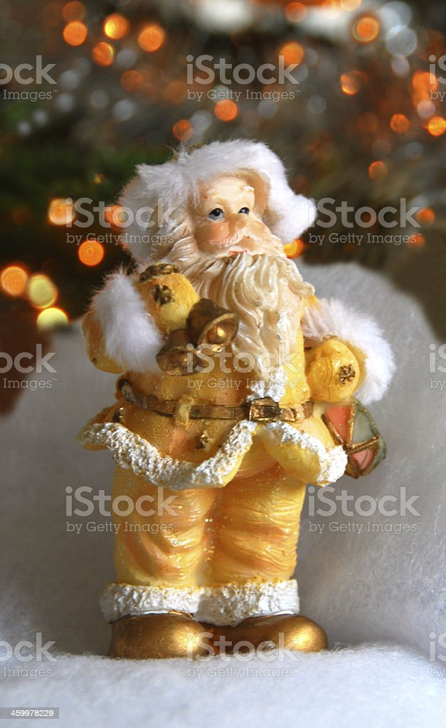 Santa Claus toy infront of a Christmas tree. stock photo