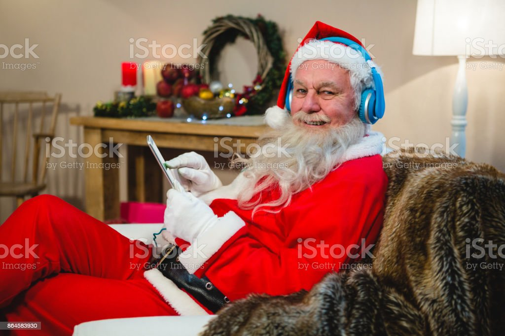 Santa claus using digital tablet at home during christmas time stock photo