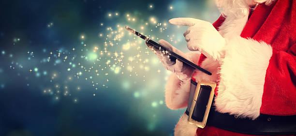 santa claus using tablet in snowy night - weihnachtsideen stock-fotos und bilder