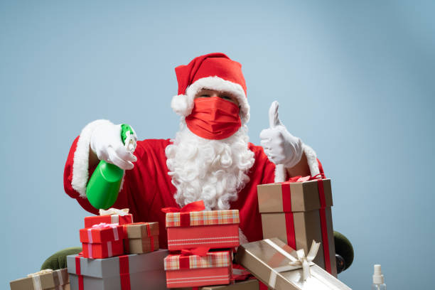 Santa Claus Wearing Protective Gloves Disinfecting Gift Box For Christmas stock photo