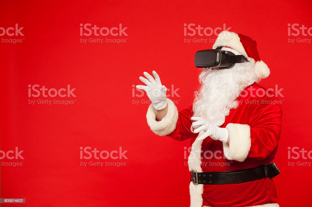 Santa Claus wearing virtual reality goggles, on a red background foto de stock royalty-free