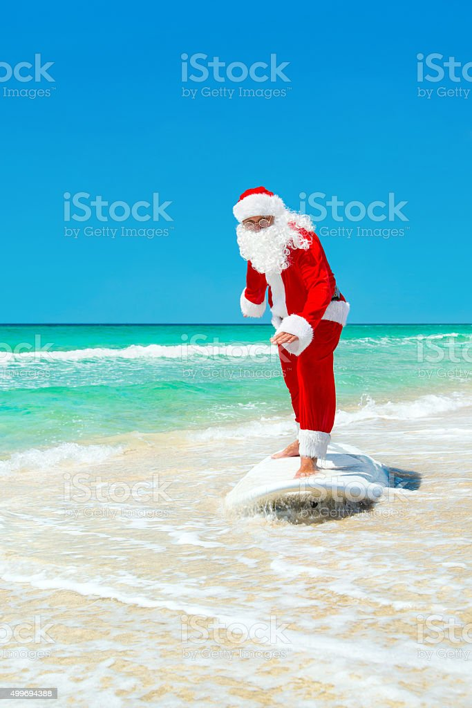 Santa Claus windsurfer go surfing with surfboard at ocean waves stock photo