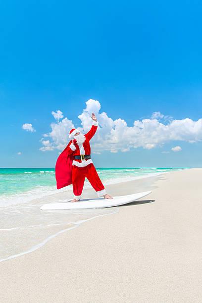 santa claus windsurfer auf dem surfbrett-mit weihnachten-tasche am strand - windbeutel stock-fotos und bilder