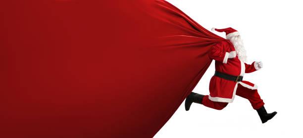 santa claus mit einer großen tasche auf der flucht - santa stock-fotos und bilder