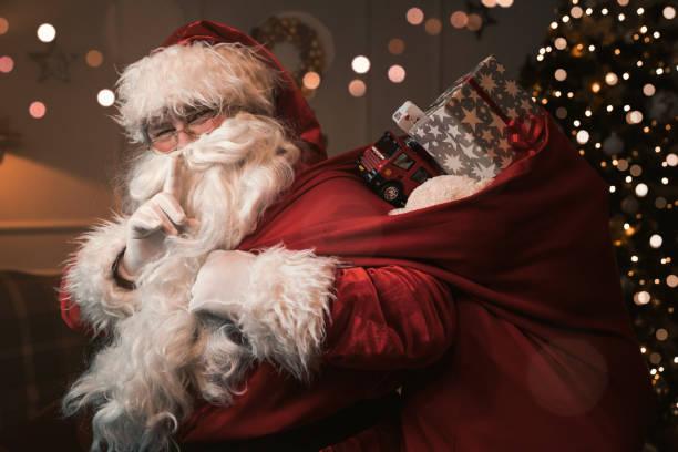 santa claus mit finger auf die lippen - santa stock-fotos und bilder