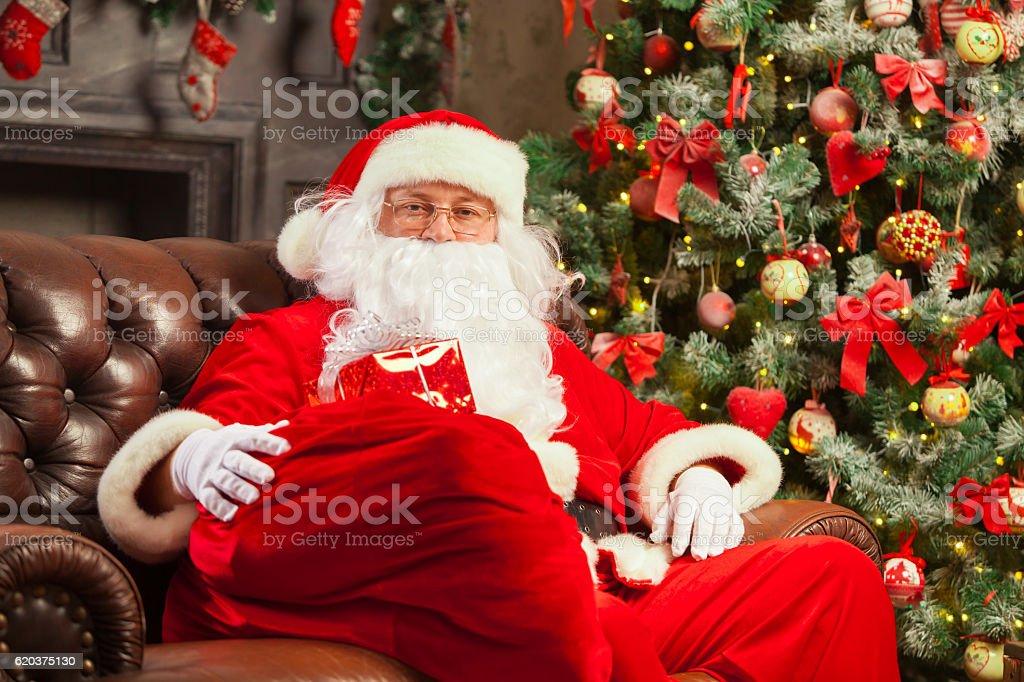 Santa Claus with giftbox on background of sparkling firtree. Christmas zbiór zdjęć royalty-free