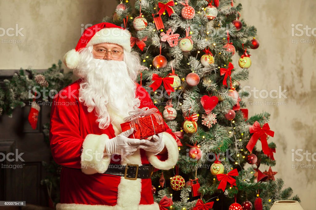 Santa Claus with giftbox on background of sparkling firtree zbiór zdjęć royalty-free
