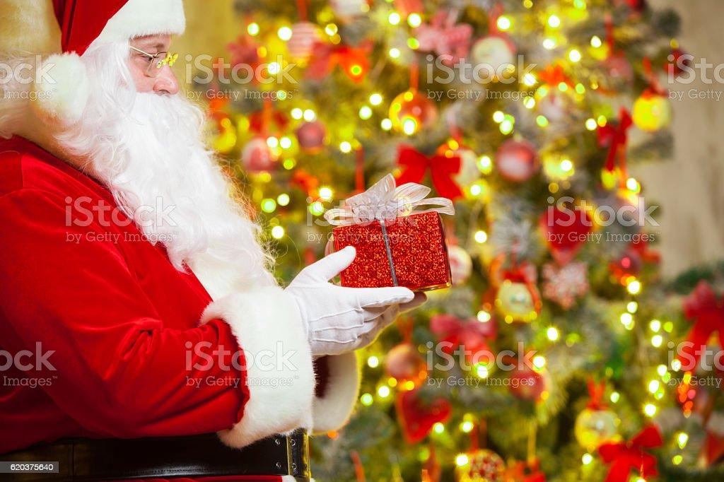 Santa Claus with giftbox on background of sparkling firtree zbiór zdjęć royalty-free