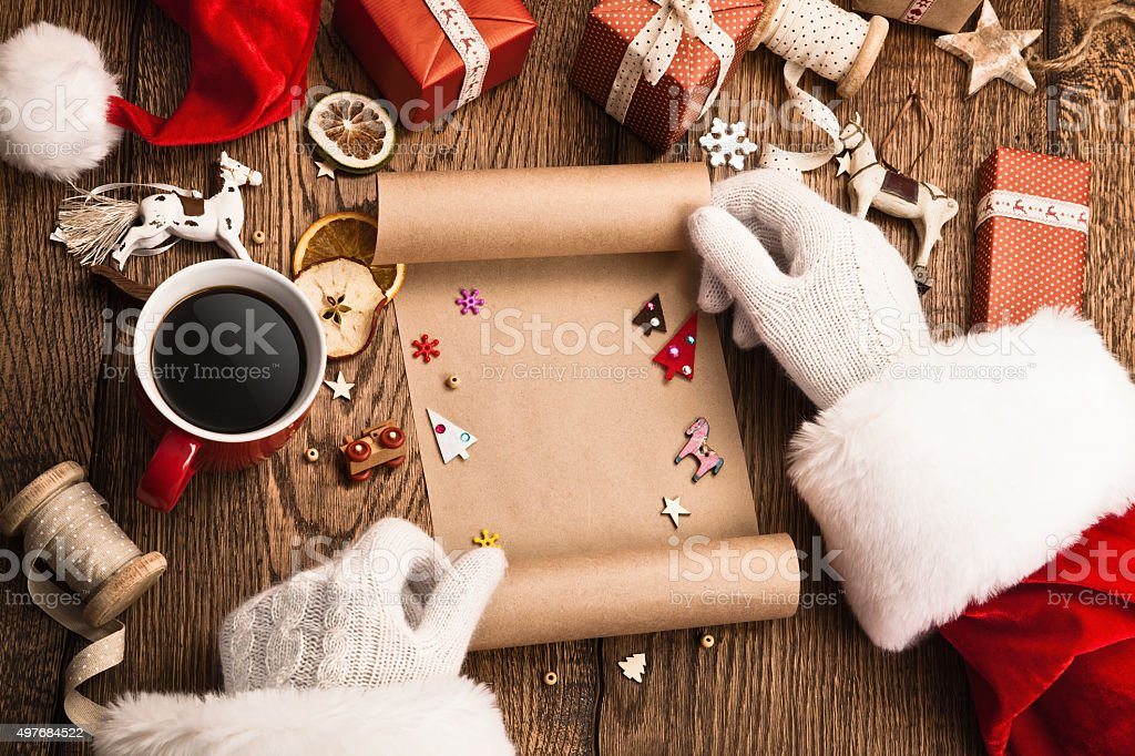 Santa Claus with gifts and wish list stock photo