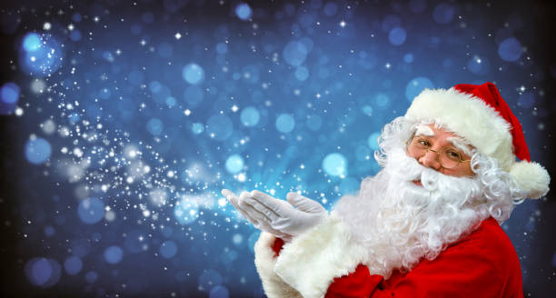 santa claus with magic light in his hands - santa claus stock photos and pictures