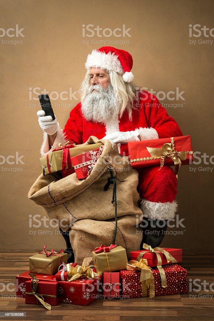 santa claus with many gifts and a phone stock photo