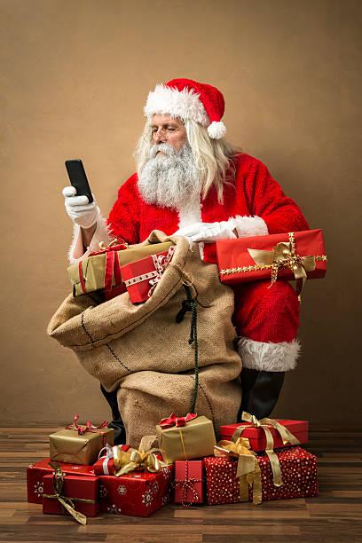 santa claus mit viele geschenke und telefon - weihnachtsprogramm stock-fotos und bilder