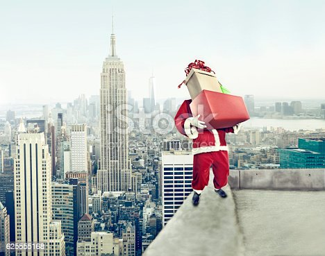 istock Santa Claus with presents on rooftop 625555168