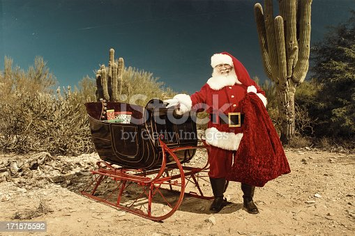 Santa Claus standing next to his sleigh in a desert setting surrounded by cacti.  Santa Claus has one hand on a sleigh and is looking forward.  The ground is sandy and along with the cacti desert brush and bushes can be seen.
