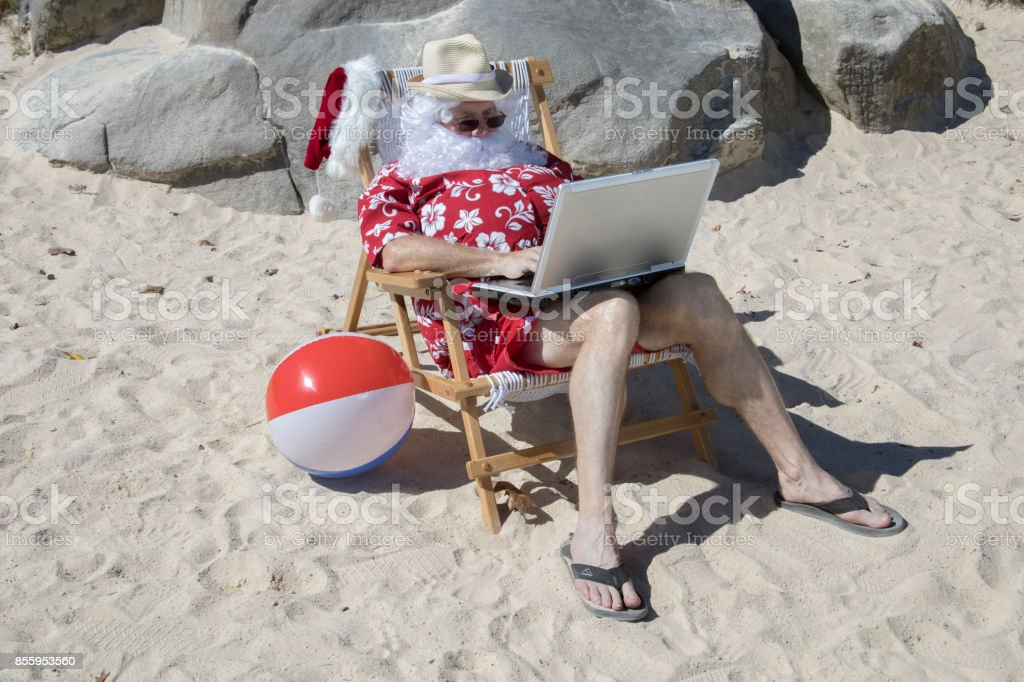 Santa Claus working on beach with laptop computer stock photo