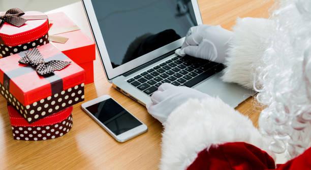 santa claus working on laptop - weihnachtsprogramm stock-fotos und bilder