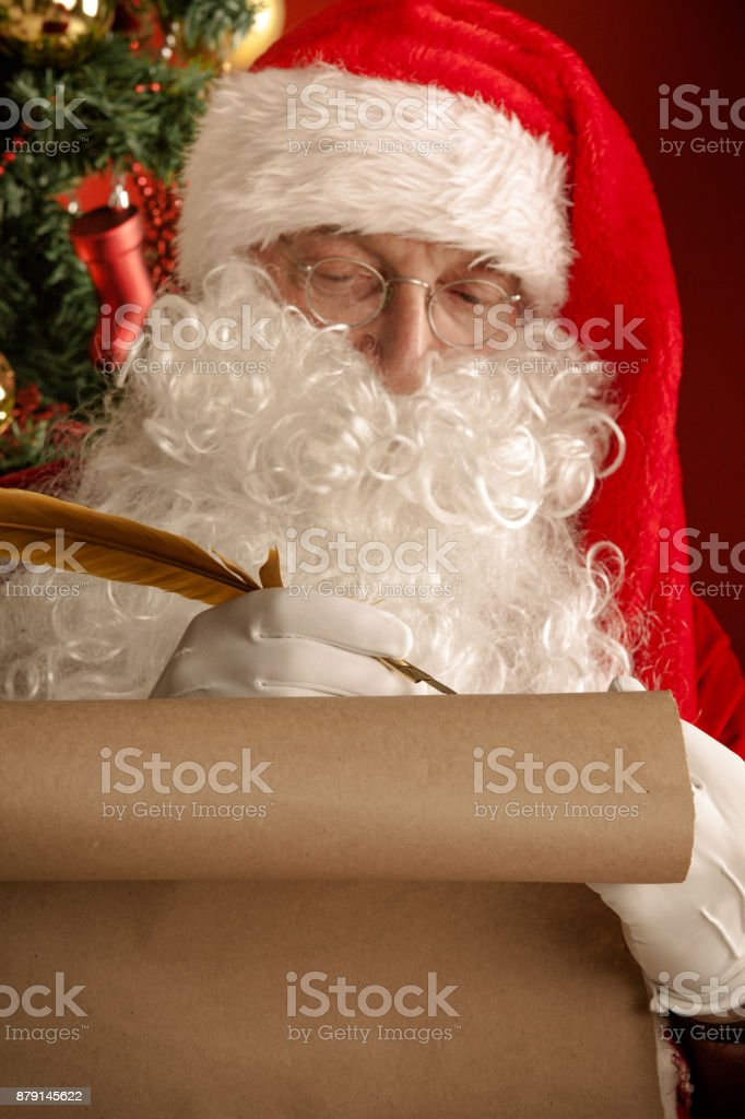 Santa Claus writing on old paper stock photo