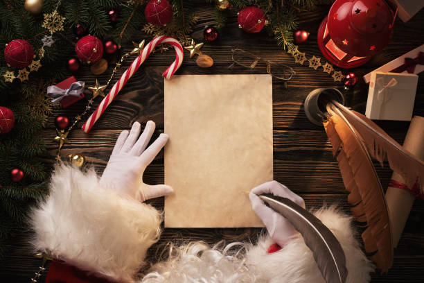 santa claus writting letter on wooden table - babbo natale foto e immagini stock