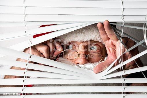 Santa Clause peeks through a window blind