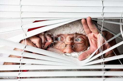 istock Santa Clause peeks through a window blind 1028268944