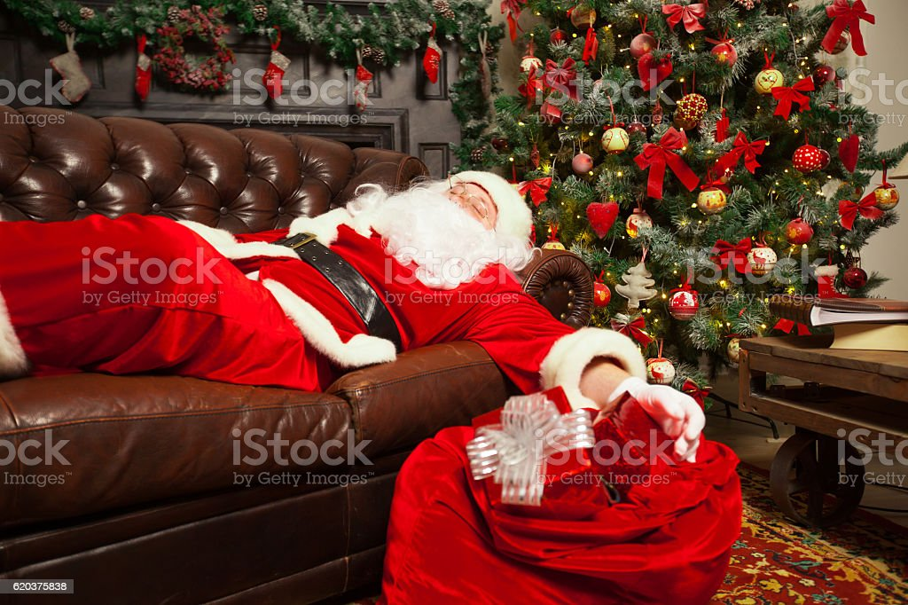 Santa Clause snoozing in a decorated living room with sack foto de stock royalty-free