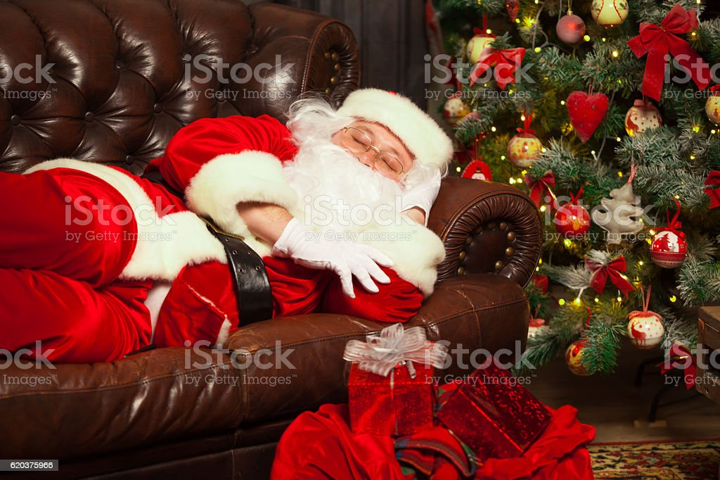 Santa Clause snoozing in a decorated living room with sack zbiór zdjęć royalty-free