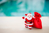 Santa Clause with red gift bag over blurred blue background, Christmas concept