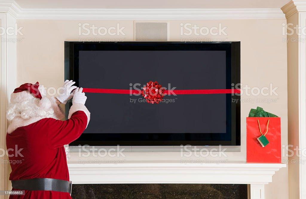 Santa Clause Wrapping a Big Screen TV stock photo