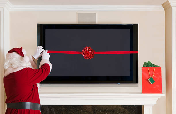 Santa Clause Wrapping a Big Screen TV stock photo