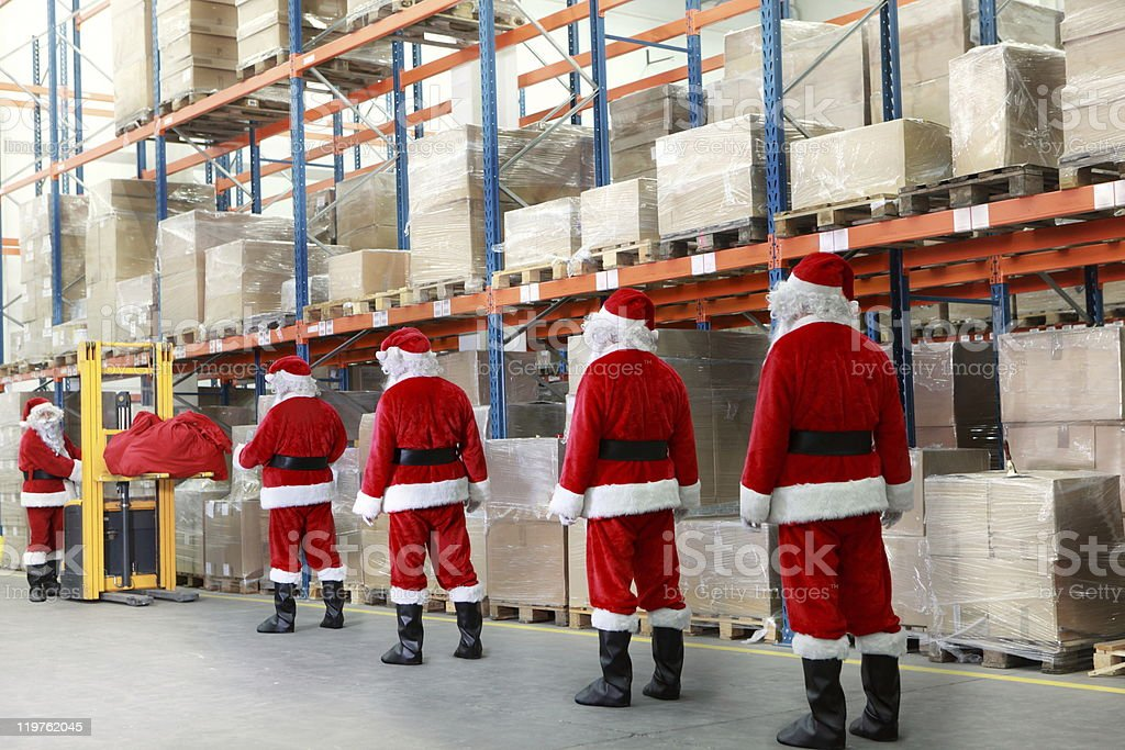 santa clauses in the line for  sacks  of gifts royalty-free stock photo