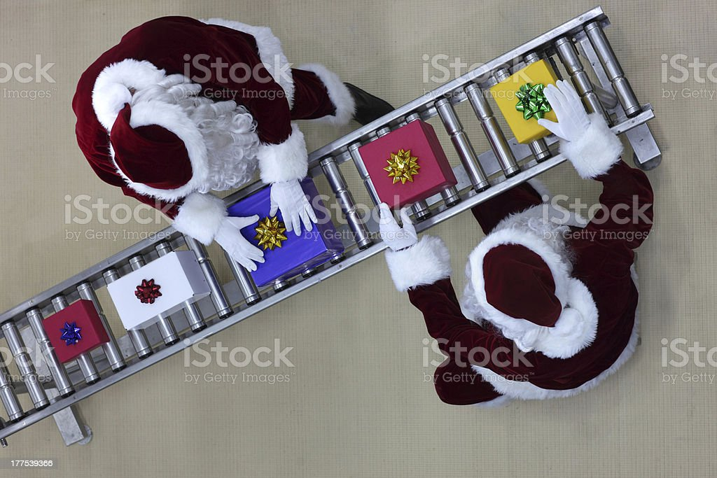 santa clauses working at production line in presents factory royalty-free stock photo