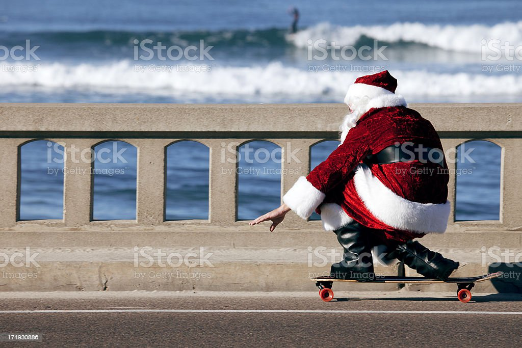 Santa Cruising on a Skateboard at the beach stock photo